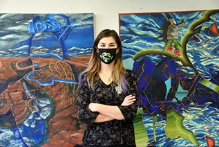 Woman wearing mask standing in front of paintings.